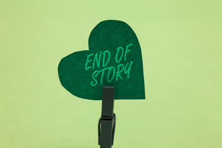 Writing note showing End Of Story. Business photo showcasing Emphasize that nothing to add Literature writing Journalism Clothespin holding green paper heart important romantic message ideas Standard-Bild