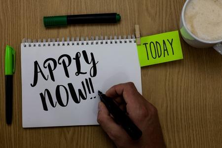 La scrittura della nota mostra Applica ora. Business photo vetrina per fare una domanda formale per un lavoro subito Agire uomo con notebook marcatore clothepin promemoria tavolo in legno tazza di caffè Archivio Fotografico - 106691416