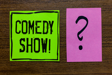 Handwriting text Comedy Show. Concept meaning Funny program Humorous Amusing medium of Entertainment Green paper note Important reminder pink question mark wooden background