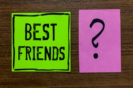 Handwriting text Best Friends. Concept meaning A person you value above other persons Forever buddies Green paper note Important reminder pink question mark wooden background Stock Photo