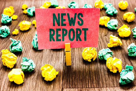 Word writing text News Report. Business concept for spoken or written account of something that one has observed Clothespin holding pink note paper crumpled papers several tries mistakes