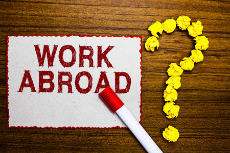 Text sign showing Work Abroad. Conceptual photo Immersed in a foreign work environment Job Overseas Non Local White paper marker crumpled papers forming question mark wooden background