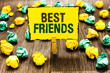 Writing note showing Best Friends. Business photo showcasing A person you value above other persons Forever buddies Clothespin holding yellow note paper crumpled papers several tries Stock Photo