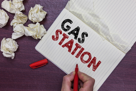 Handwriting text Gas Station. Concept meaning for servicing motor vehicles especially with gasoline and oil Man holding marker notebook page crumpled papers several tries mistakes