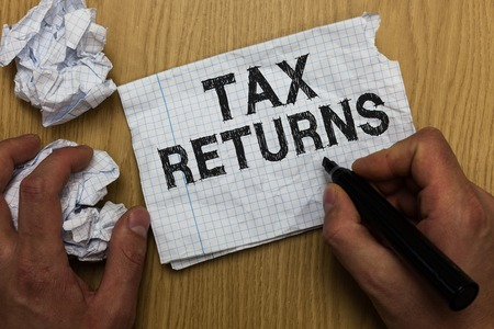 Writing note showing Tax Returns. Business photo showcasing Tax payer financial information Tax Liability and Payment report Man holding marker notebook paper crumpled papers several tries