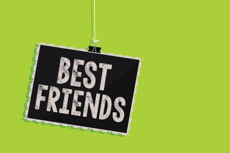Conceptual hand writing showing Best Friends. Business photo text A person you value above other persons Forever buddies Hanging blackboard message communication sign green background Stock Photo