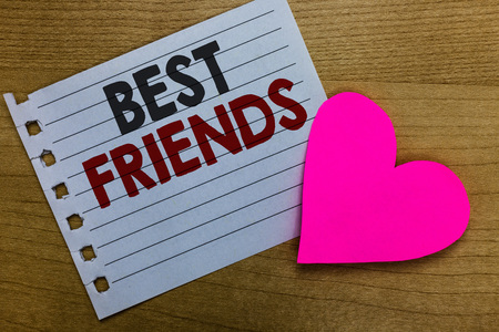Conceptual hand writing showing Best Friends. Business photo showcasing A person you value above other persons Forever buddies Notebook paper Romantic ideas heart feelings Wooden table