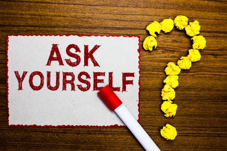 Text sign showing Ask Yourself. Conceptual photo Thinking the future Meaning and Purpose of Life Goals White paper marker crumpled papers forming question mark wooden background