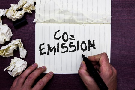 Word writing text Co2 Emission. Business concept for Releasing of greenhouse gases into the atmosphere over time Man holding marker notebook page crumpled papers several tries mistakes Фото со стока