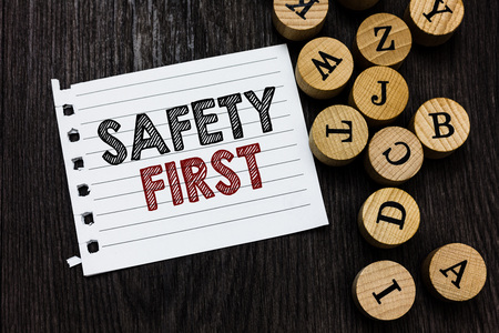 Word writing text Safety First. Business concept for Avoid any unnecessary risk Live Safely Be Careful Pay attention Piece notebook paper circle letters ideas inspiration wooden background