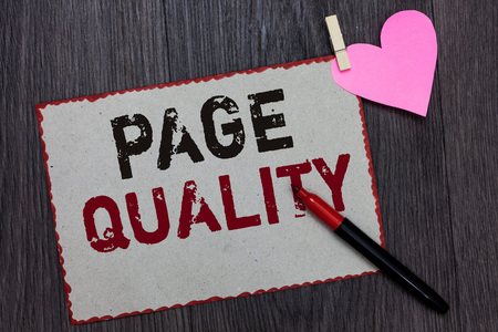 Text sign showing Page Quality. Conceptual photo Effectiveness of a website in terms of appearance and function White page red borders marker clothespin holds paper heart wood background 免版税图像