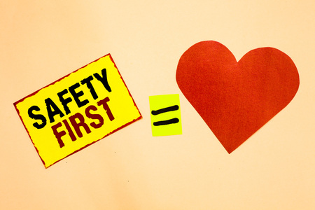 Handwriting text writing Safety First. Concept meaning Avoid any unnecessary risk Live Safely Be Careful Pay attention Yellow piece paper reminder equal sign red heart sending romantic feelings Stockfoto