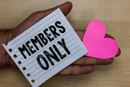Text sign showing Members Only. Conceptual photo Limited to an individual belongs to a group or an organization Man holding piece notebook paper heart Romantic ideas messages feelings