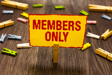 Text sign showing Members Only. Conceptual photo Limited to an individual belongs to a group or an organization Clothespin holding yellow paper note several clothespins wooden floor