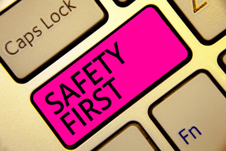 Text sign showing Safety First. Conceptual photo Avoid any unnecessary risk Live Safely Be Careful Pay attention Keyboard pink key Intention create computer computing reflection document Stockfoto