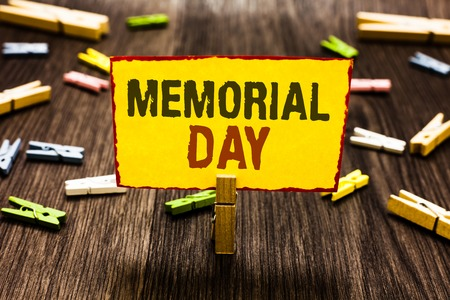 Handwriting text writing Memorial Day. Concept meaning To honor and remembering those who died in military service Clothespin holding yellow paper note several clothespins wooden floor