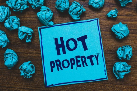 Word writing text Hot Property. Business concept for Something which is sought after or is Heavily Demanded Blue paper note reminder crumpled papers several tries wooden background Foto de archivo