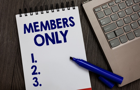 Handwriting text Members Only. Concept meaning Limited to an individual belongs to a group or an organization Open notebook white page black marker computer keyboard wooden background