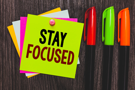Conceptual hand writing showing Stay Focused. Business photo showcasing Be attentive Concentrate Prioritize the task Avoid distractions Paper notes Communicate ideas Markers Wooden background