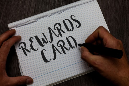 Writing note showing Rewards Card. Business photo showcasing Help earn cash points miles from everyday purchase Incentives Man hand holding marker communicating ideas reflections squared paper