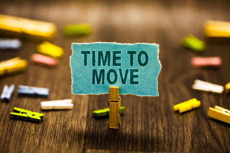 Word writing text Time To Move. Business concept for Best period to transfer Relocation Change the current path Clothespin holding blue paper note reminder clothespins wooden floor Archivio Fotografico