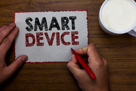 Word writing text Smart Device. Business concept for Electronic gadget that able to connect share interact with user Man holding marker communicating ideas piece paper wooden table cup coffee