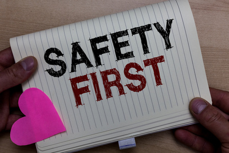Word writing text Safety First. Business concept for Avoid any unnecessary risk Live Safely Be Careful Pay attention Man holding notebook paper heart Romantic ideas messages Wooden background