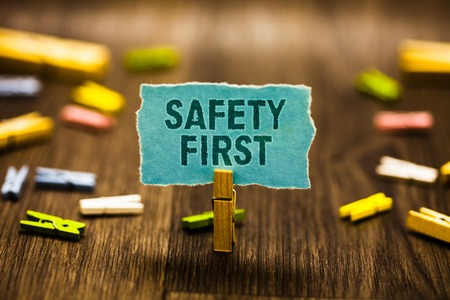Word writing text Safety First. Business concept for Avoid any unnecessary risk Live Safely Be Careful Pay attention Clothespin holding blue paper note reminder clothespins wooden floor Stockfoto