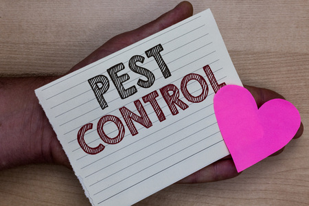 Word writing text Pest Control. Business concept for Killing destructive insects that attacks crops and livestock Man holding piece notebook paper heart Romantic ideas messages feelings Stock fotó