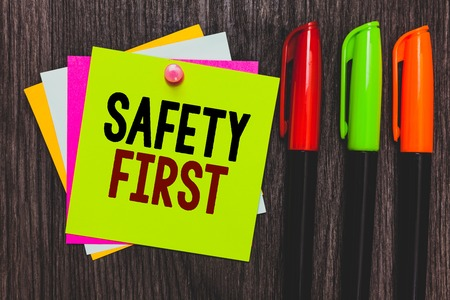 Conceptual hand writing showing Safety First. Business photo showcasing Avoid any unnecessary risk Live Safely Be Careful Pay attention Paper notes Communicate ideas Markers Wooden background