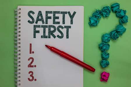 Handwriting text Safety First. Concept meaning Avoid any unnecessary risk Live Safely Be Careful Pay attention Notebook marker crumpled papers forming question mark green background