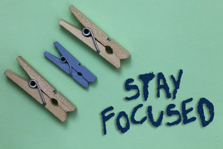 Conceptual hand writing showing Stay Focused. Business photo showcasing Be attentive Concentrate Prioritize the task Avoid distractions Three brown blue vintage clear background Holding things