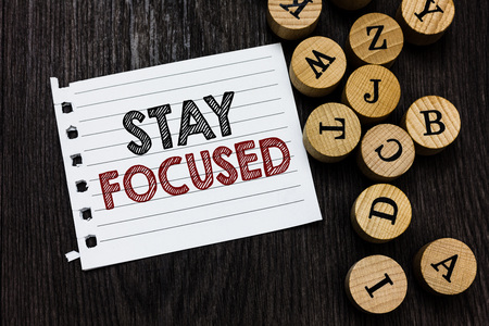 Word writing text Stay Focused. Business concept for Be attentive Concentrate Prioritize the task Avoid distractions Piece notebook paper circle letters ideas inspiration wooden background