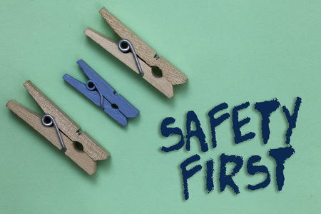 Conceptual hand writing showing Safety First. Business photo showcasing Avoid any unnecessary risk Live Safely Be Careful Pay attention Three brown blue vintage clear background Holding things