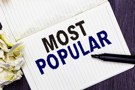 Conceptual hand writing showing Most Popular. Business photo text Liked Followed Enjoyed by majority of the people in a society Marker over notebook crumpled papers several tries mistakes