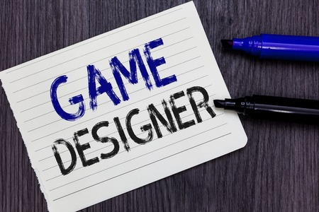 Writing note showing Game Designer. Business photo showcasing Campaigner Pixel Scripting Programmers Consoles 3D Graphics Notebook Paper Reminder Communicating ideas Markers Wooden background Banco de Imagens