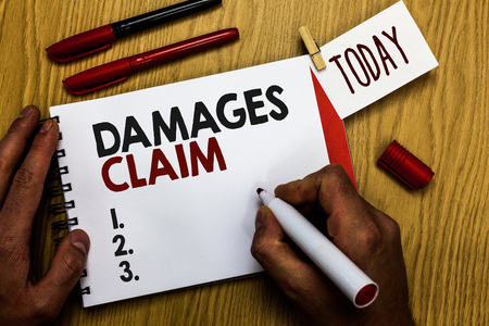Handwriting text writing Damages Claim. Concept meaning Demand Compensation Litigate Insurance File Suit Man holding marker notebook clothespin reminder wooden table cup coffee