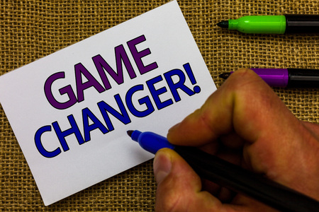 Text sign showing Game Changer. Conceptual photo Sports Data Scorekeeper Gamestreams Live Scores Team Admins Man hand holding marker white paper communicating ideas Jute background