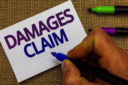 Text sign showing Damages Claim. Conceptual photo Demand Compensation Litigate Insurance File Suit Man hand holding marker white paper communicating ideas Jute background Imagens