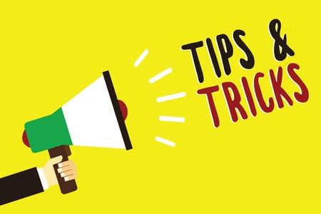 Text sign showing Tips and Tricks. Conceptual photo Steps Lifehacks Handy advice Recommendations Skills Man holding megaphone loudspeaker yellow background message speaking loud
