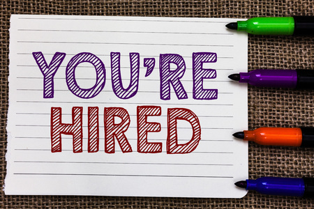 Conceptual hand writing showing You re are Hired. Business photo showcasing New Job Employed Newbie Enlisted Accepted Recruited Notebook Paper Important reminder Markers Jute background