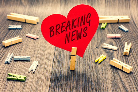 Word writing text Breaking News. Business concept for Special Report Announcement Happening Current Issue Flashnews Clothespin holding red paper heart several clothespins wooden floor romance