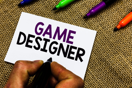 Writing note showing Game Designer. Business photo showcasing Campaigner Pixel Scripting Programmers Consoles 3D Graphics Man hand holding marker white paper communicating idea Jute background