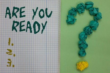 Text sign showing Are You Ready. Conceptual photo Alertness Preparedness Urgency Game Start Hurry Wide awake Notebook paper crumpled papers forming question mark green background 写真素材