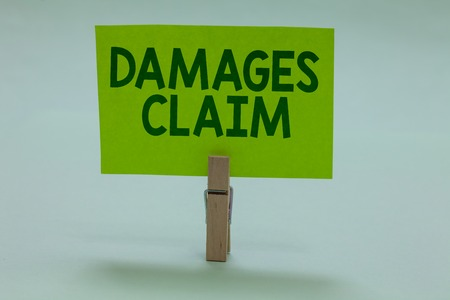 Conceptual hand writing showing Damages Claim. Business photo showcasing Demand Compensation Litigate Insurance File Suit Clothespin holding green paper important message ideas