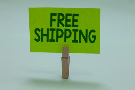 Conceptual hand writing showing Free Shipping. Business photo showcasing Freight Cargo Consignment Lading Payload Dispatch Cartage Clothespin holding green paper important message ideas Фото со стока