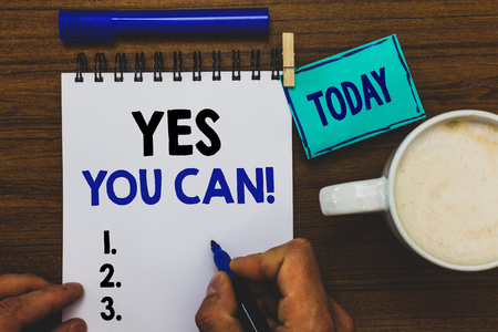 Conceptual hand writing showing Yes You Can. Business photo text Positivity Encouragement Persuade Dare Confidence Uphold Man holding marker notebook clothepin reminder wooden table coffee Banco de Imagens