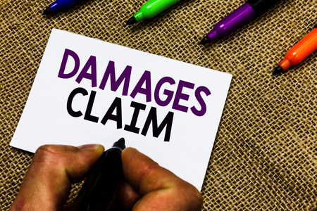 Writing note showing Damages Claim. Business photo showcasing Demand Compensation Litigate Insurance File Suit Man hand holding marker white paper communicating idea Jute background