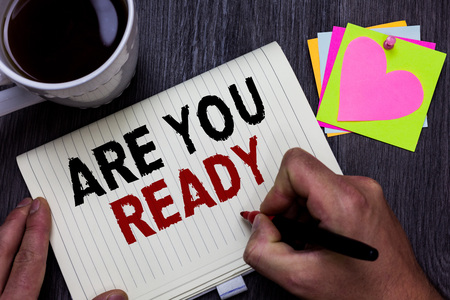Conceptual hand writing showing Are You Ready. Business photo text Alertness Preparedness Urgency Game Start Hurry Wide awake Man holding marker giving ideas wooden table cup coffee hearts