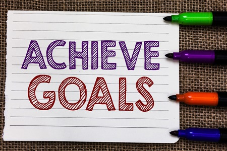 Conceptual hand writing showing Achieve Goals. Business photo showcasing Results oriented Reach Target Effective Planning Succeed Notebook Paper Important reminder Markers Jute background